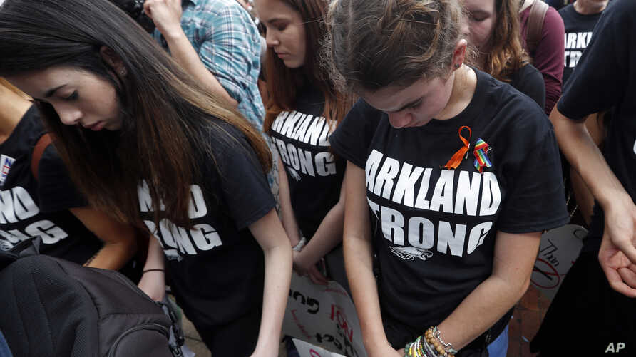 Student survivors from Marjory Stoneman Douglas High School bow their heads as the names of shooting victims are read, at a rally for gun-control reform on the steps of the state Capitol in Tallahassee, Fla., Feb. 21, 2018.