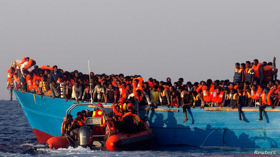A rescue boat of the Spanish NGO Proactiva approaches an overcrowded wooden vessel with migrants from Eritrea, off the Libyan coast in Mediterranean Sea, August 29, 2016.