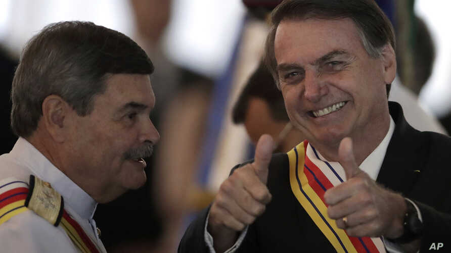Brazil's President Jair Bolsonaro flashes two thumbs up standing next to Adm. Marcus Vinicius Oliveira dos Santos, Supreme Military Court president, who presented Bolsonaro with the Order of Military Judicial Merit, in Brasilia, Brazil, March 28, 201
