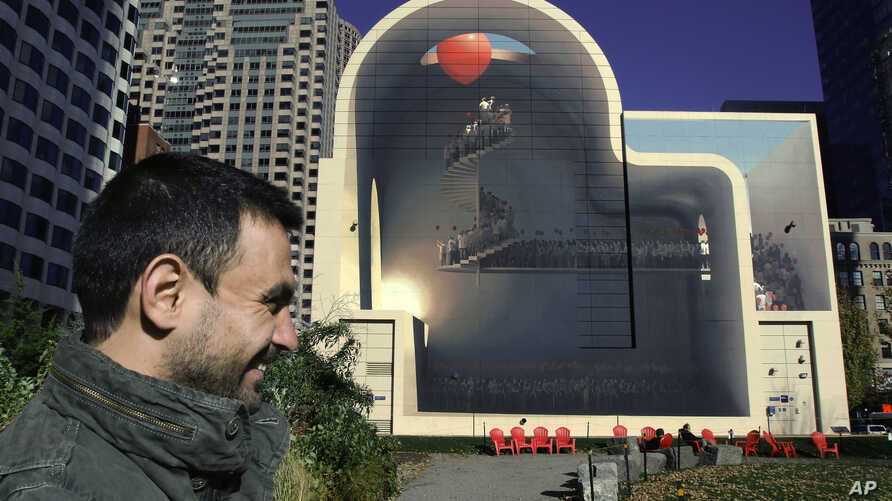 "In this Nov. 11, 2016, photo, Mehdi Ghadyanloo, from Tehran, Iran, stands beside his mural, ""Spaces of Hope,"" on the Rose Kennedy Greenway in Boston. The artwork is an expression of optimism he hopes can lead to better understanding between the peopl"