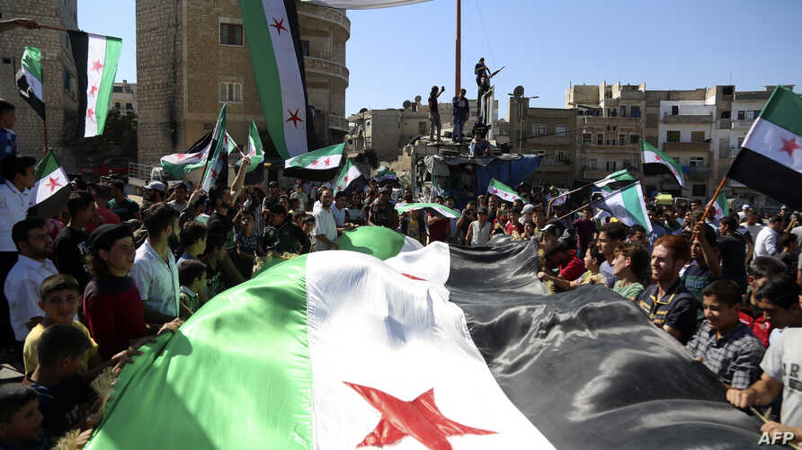 Syrian protesters, wearing the colors of opposition, attend an anti-government demonstration in the rebel-held northern Syrian city of Idlib, Sept. 28, 2018.