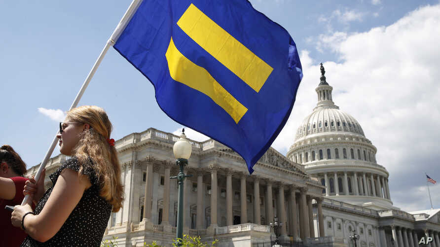 """A supporter of LGBT rights holds up an """"equality flag"""" on Capitol Hill in Washington, July 26, 2017, during an event held by Rep. Joe Kennedy, D-Mass., in support of transgender members of the military, in response to President Donald Trump's declara"""