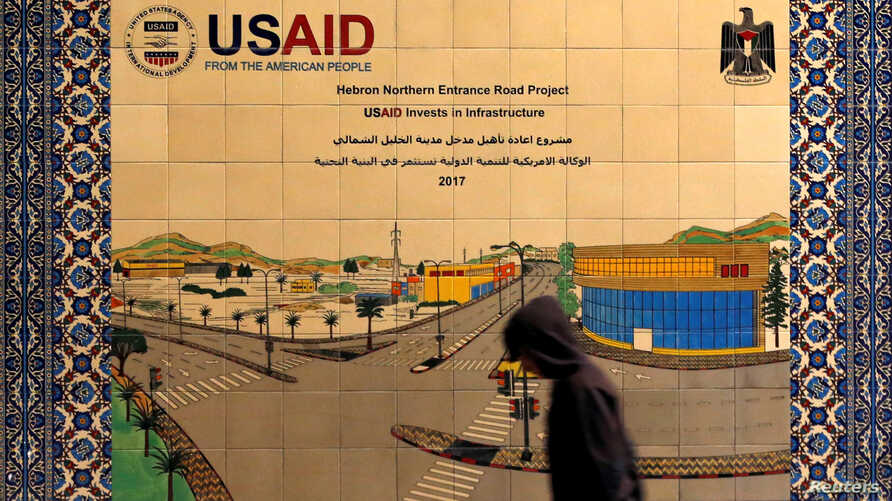A Palestinian walks past a ceramic sign of a U.S. Agency for International Development (USAID) project in Hebron in the Israeli-occupied West Bank, Jan. 31, 2019.