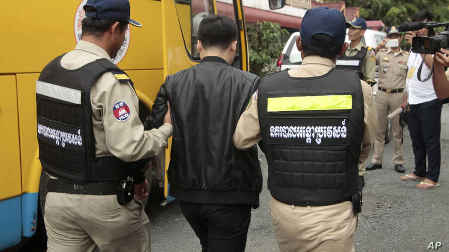 A Chinese national arrested over an alleged internet scam is escorted by police officers to be deported at the immigration office in Phnom Penh, Cambodia, July 26, 2017.