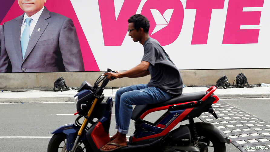 A man rides a motorcycle past an image of Maldives President Abdulla Yameen on a road ahead of the presidential election in Male, Maldives, Sept. 19, 2018.