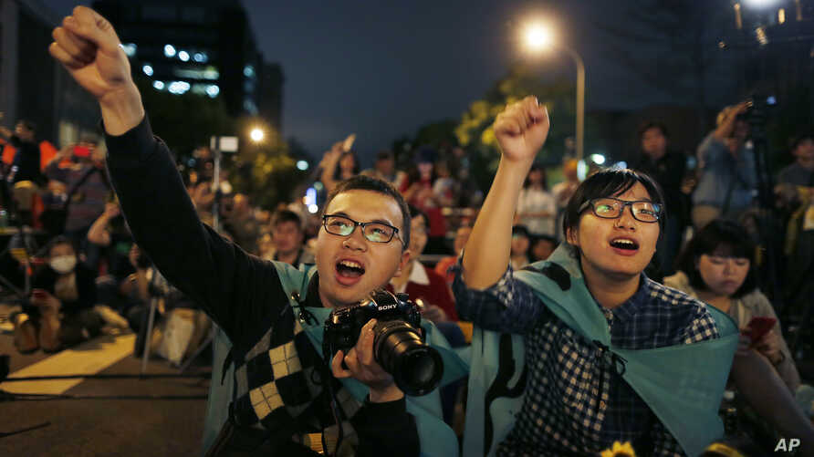 Students cheer on speakers during a gathering to mark the first anniversary of student groups stormed the parliament in Taipei, Taiwan, March 18, 2015.