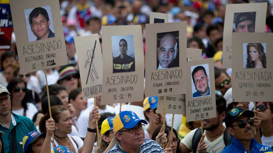 Demonstrators hold up posters with images of Venezuelans who were killed in the past two weeks during the recent unrest, at a rally with human rights activists in Caracas, Venezuela, Feb. 28, 2014.