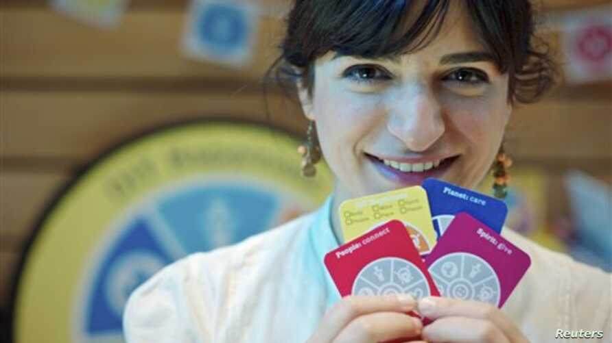 Joanna Choukeir shows some of the cards from a DIY Happiness card game, at the launch of  'Action For Happiness' encouraging meditation, hugging and kindness, in London, April 12, 2011.