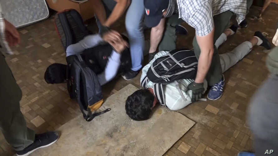 In this undated video grab provided by the RU-RTR Russian television via APTN on Aug. 14, 2017, Russian FSB officers arrest two men on suspicion of plotting a series of attacks outside Moscow.