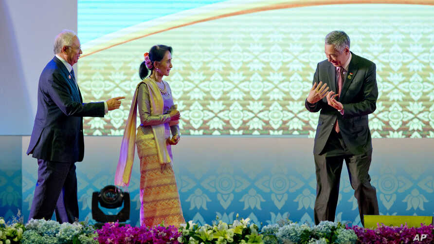Singapore's Prime Minister Lee Hsien Loong, right gestures to Myanmar's Foreign Minister Aung San Suu Kyi, to move in closer for the group hand shake as Malaysia's Prime Minister Najib Razak, left, watches during the opening ceremony of the 28th and