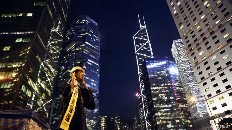 A woman holds a banner and a helmet, symbols of the pro-democracy movement, as she has her picture taken in part of Hong Kong's financial central district occupied by protesters, Oct. 29, 2014.
