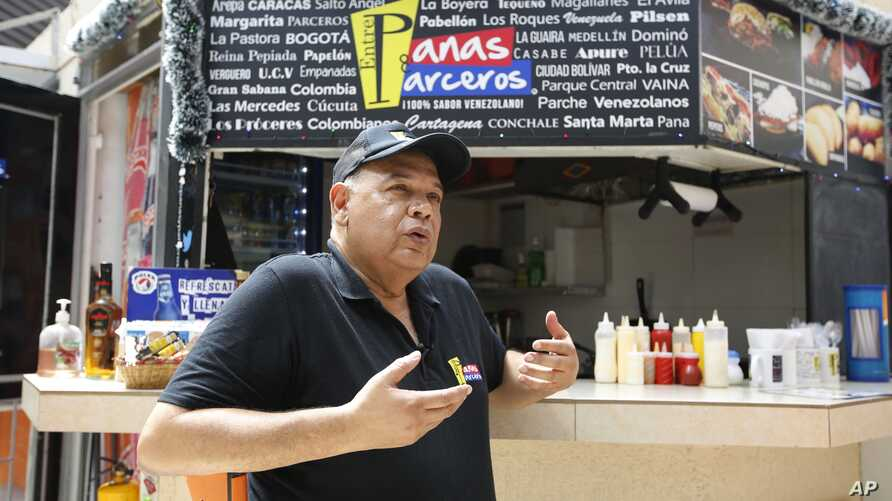 Venezuelan national Fernando Fernandez gestures as he is interviewed in front of his fast food stand in Bogota, Colombia, Dec. 22, 2017. Fernandez said he left Venezuela two years ago because of the country's economic crisis.