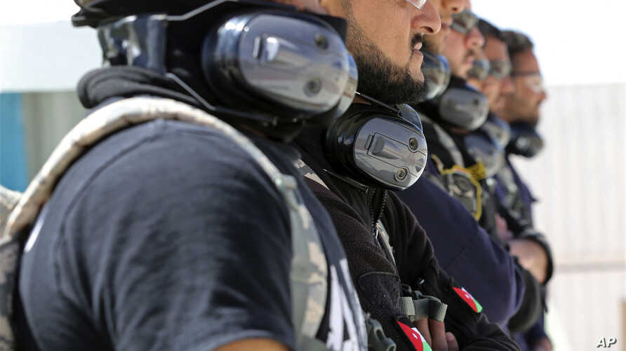 A SWAT team from Iraq's Anbar province watches U.S. instructors staging a training drill on how to respond to a bomb threat and how to detonate the device at the Jordan International Police Training Center, in the Jordanian town of al-Muwaqqar, about