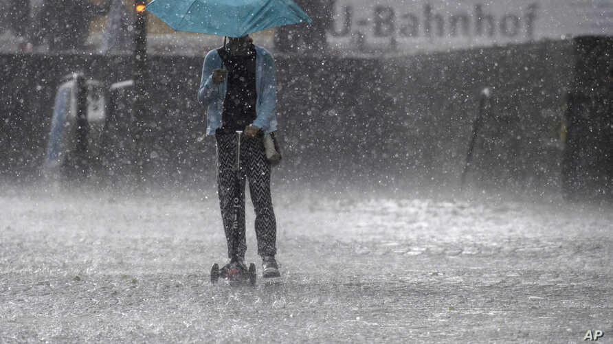 FILE - A girl with a scooter drives through a hailstorm in Munich, Germany, May 19, 2017.