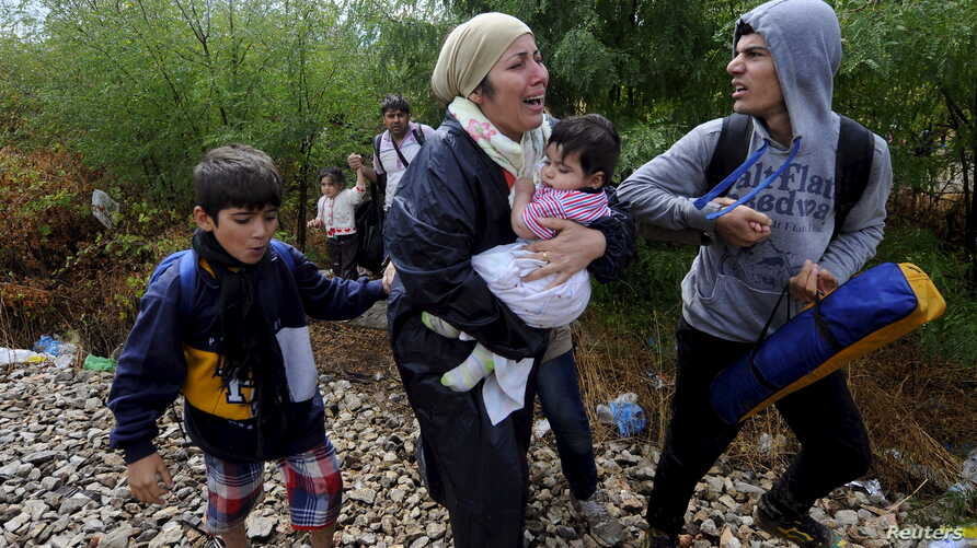 FILE - Migrants cry and walk towards Gevgelija in Macedonia after crossing Greece's border, Macedonia, Aug. 22, 2015.