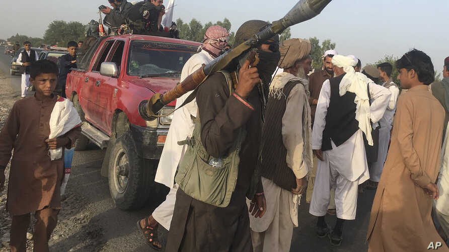 FILE - Taliban fighters gather in Surkhroad district of Nangarhar province, east of Kabul, Afghanistan.