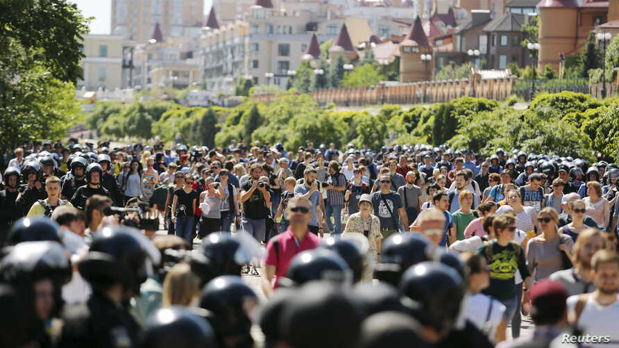 FILE - Interior Ministry members stand guard as activists take part in the LGBT Equality March in Kyiv, Ukraine, June 6, 2015.