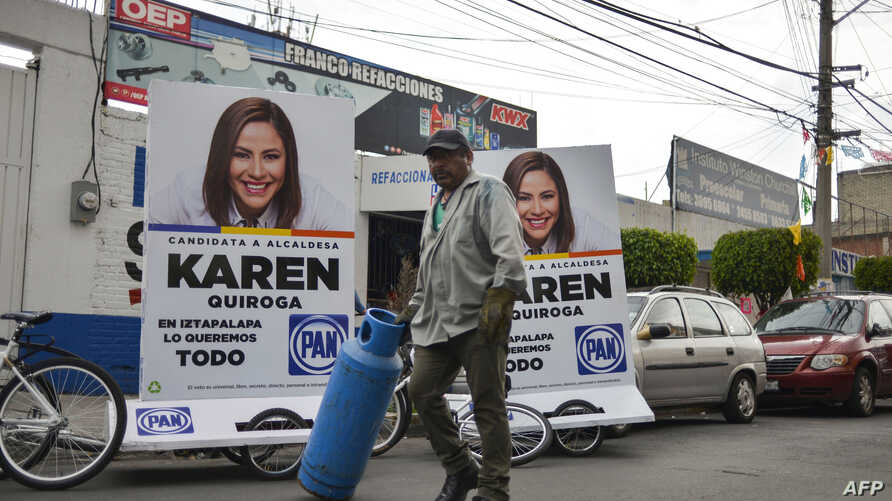 A man walks past political propaganda in the streets of the Iztapalapa neighborhood in Mexico City on June 26, 2018. Elections will take place in Mexico on July 1. Since campaigns kicked off in September, 113 politicians have been killed across Mexic