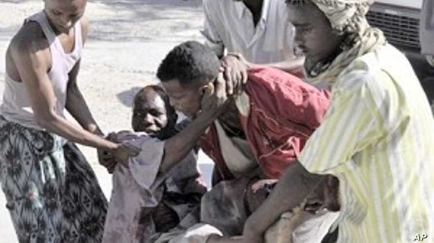 Residents assist a victim who was injured during shelling in Mogadishu's restive Bakara market (File Photo)