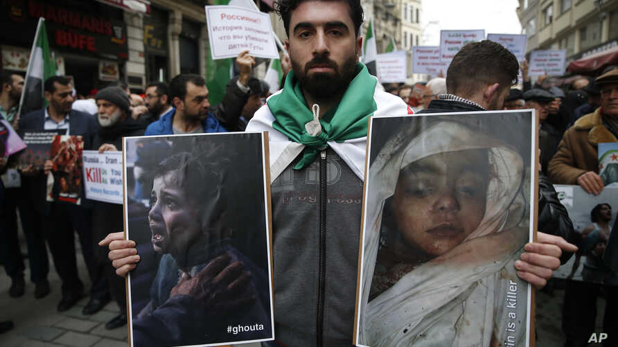 People holding pictures of victims of the airstrikes and shelling in Ghouta, a suburb of Damascus, gather during a rally outside the Russian Consulate in Istanbul, Feb. 22, 2018.