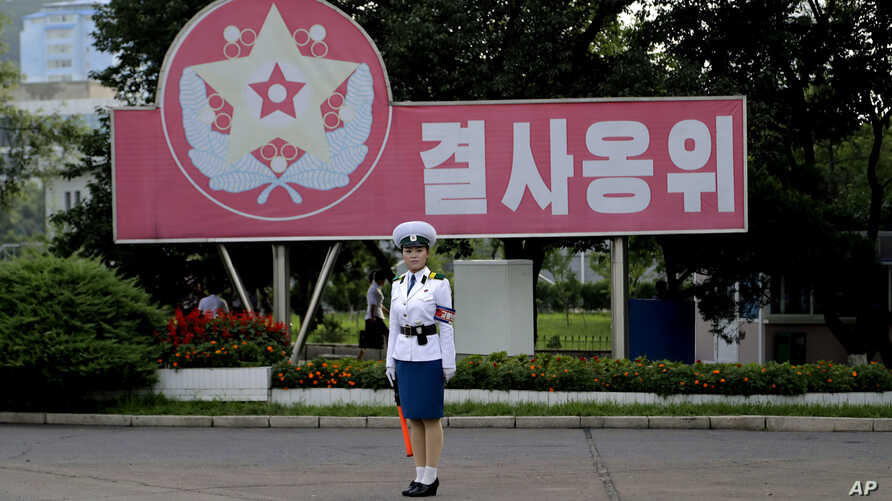"A North Korean traffic policewoman stands at a street junction in front of a propaganda slogan that reads: ""Safeguard with a do-or-die attitude,"" July 29, 2017, in Pyongyang, North Korea. Tensions between North Korea and the United States have risen"