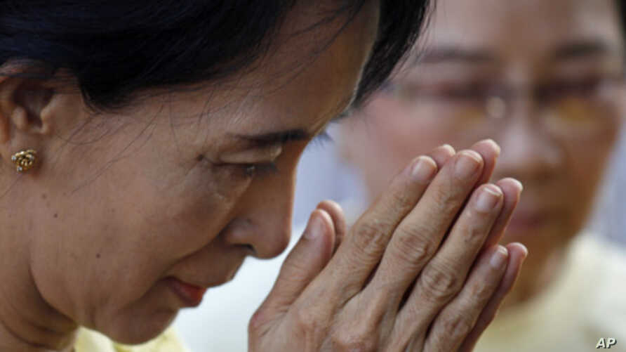 Burma's pro-democracy leader Aung San Suu Kyi gestures as she offers yellow robes to Buddhist monks in front of the National League for Democracy party's headquarters in Rangoon, Dec. 8, 2010.
