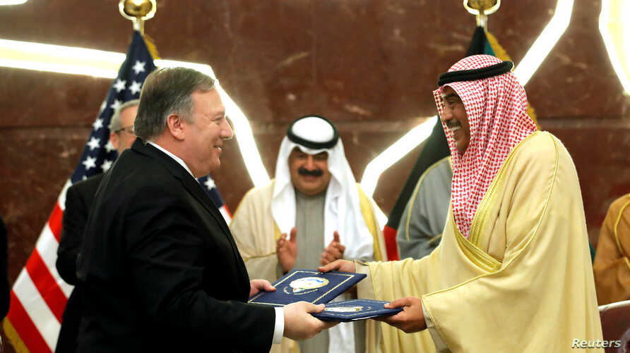 U.S. Secretary of State Mike Pompeo and Kuwait's Foreign Minister Sheikh Sabah Al-Khalid Al-Sabah exchange the signed document in Kuwait City, Kuwait, March 20, 2019.