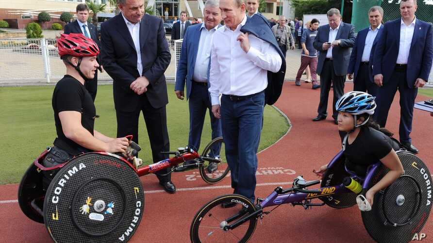 FILE - Russian President Vladimir Putin, center, speaks with athletes of the Russian Paralympic cycling team as he visits a sports training center in Sochi,  the Black Sea resort that hosted this year's Winter Olympics, Russia, Thursday, Oct. 23, 201