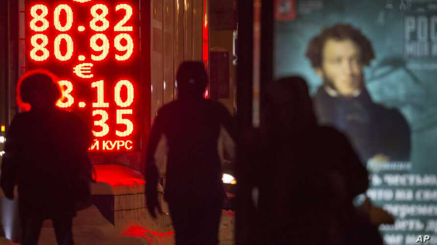 People walk past a currency exchange display board in Moscow, Russia, Jan. 20, 2016.
