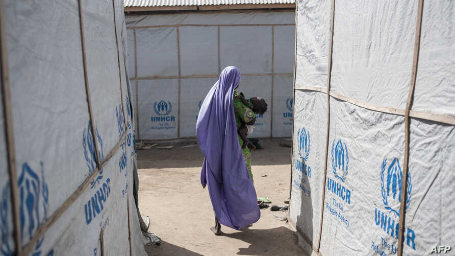 FILE - A woman carries her baby through temporary shelters provided by the Mission for the United Nations in Maiduguri, Nigeria, Dec. 7, 2016.