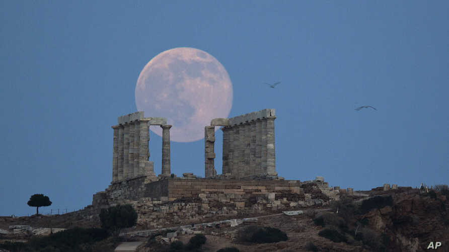 Seagulls fly as the full moon rises behind the ancient marble Temple of Poseidon at Cape Sounion, southeast of Athens, on the eve of the summer solstice on June 20, 2016.