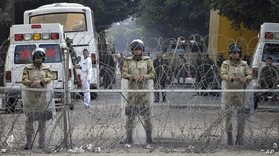 Egyptian soldiers stand behind a barbed wire fence while guarding the Cabinet building near Tahrir Square in Cairo, Egypt, Saturday, Nov. 26, 2011.