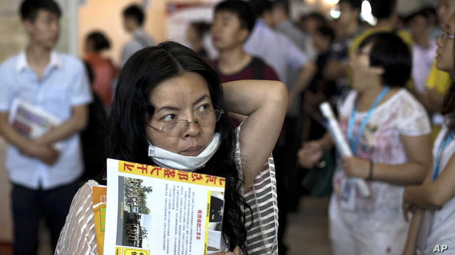 FILE - Chinese woman with her resume hunts for a job during a job fair held at the China International Exhibition Center in Beijing.