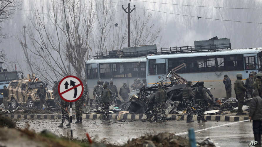 Indian paramilitary soldiers stand by the wreckage of a bus after an explosion in Pampore, Indian-controlled Kashmir, Thursday, Feb. 14, 2019.