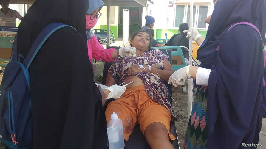 A paramedic gives treatment to an earthquake survivor outside a hospital in Donggala, Indonesia, Sulawesi Island, Sept. 28, 2018.
