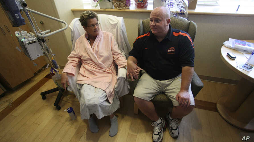 FILE - Laurie Cavanaugh holds hands with her husband Mike Cavanaugh in her hospital room after surgery at Oregon Health & Science University Hospital, in Portland, Oregon.