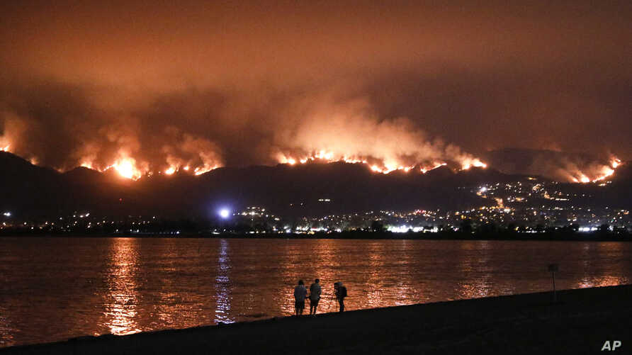 Onlookers are silhouetted against the reflection of a wildfire burning in the Cleveland National Forest in Lake Elsinore, Calif., Aug. 8, 2018.