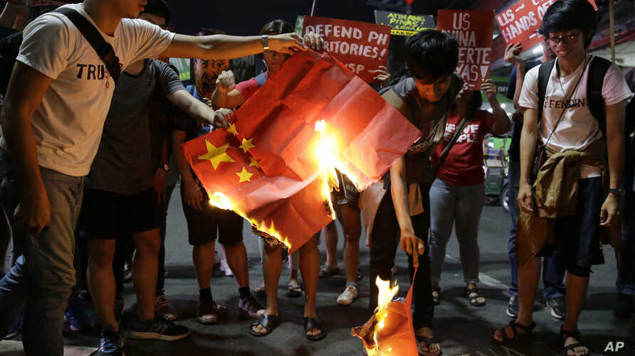 Students burn a Chinese flag as they protest against the visit of Chinese President Xi Jinping during a demonstration outside the Presidential Palace in Manila, Philippines, Nov. 20, 2018.