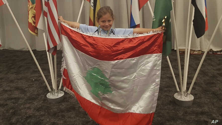 FILE - This Sept. 30, 2018 photo provides by Rochana Atmeh, shows Jennifer Maria Hektor, 8, born to a Swedish father and Rochana Atmeh, her Lebanese mother, holding a Lebanese flag, in Johannesburg, South Africa.