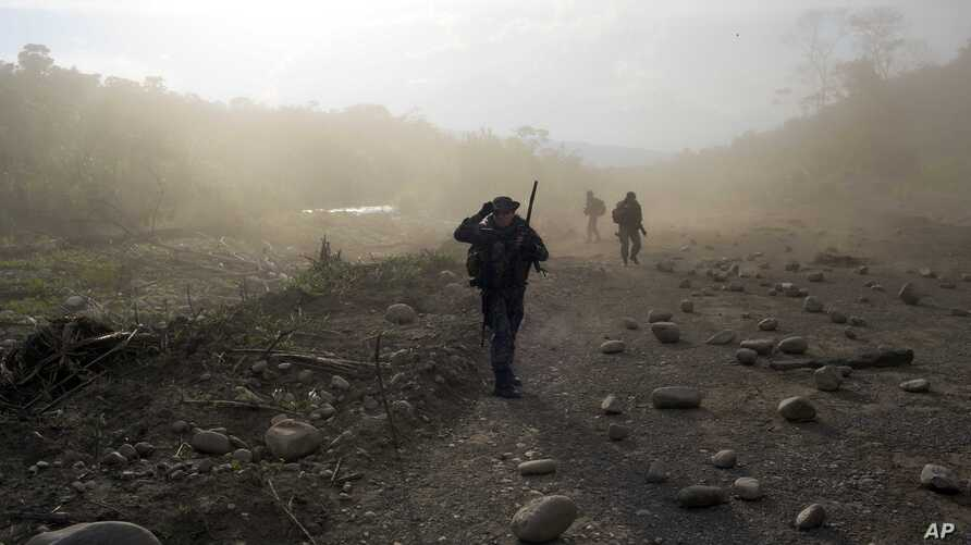 FILE - Counternarcotics officers walk in a clandestine airstrip strewn with boulders, in the Apurimac, Ene and Mantaro River Valleys, or VRAEM, the world's No. 1 coca-growing region, in Junin Peru, Sept. 19, 2014.