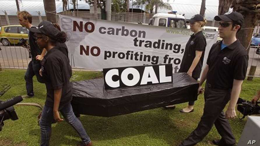 People walk with a coffin as they protest against the usage of coal during a climate change conference at the city of Durban, South Africa, December 1, 2011.