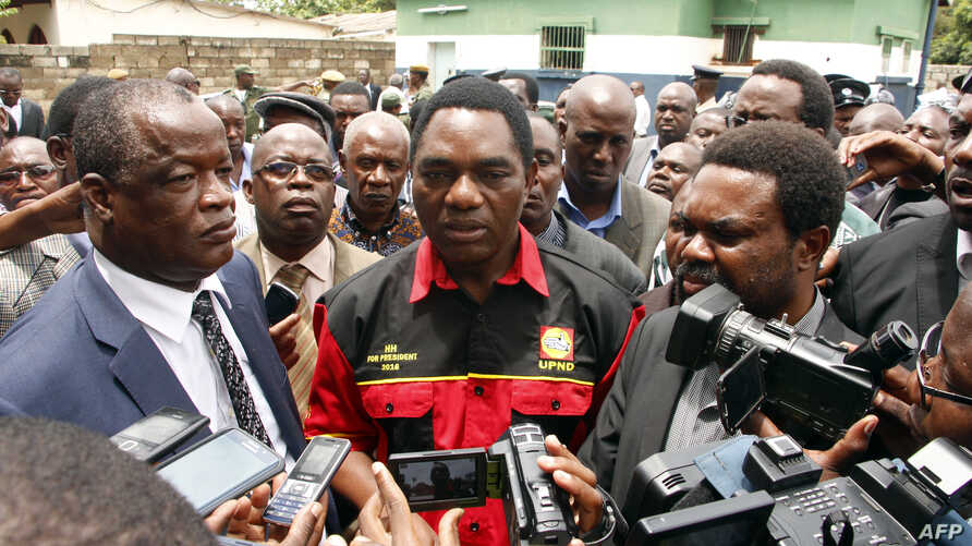 Opposition United Party for National Development president Hakainde Hichilema (C) talks to journalists before being dispersed with supporters athe Woodlands Police Station in Lusaka on March 2, 2016.