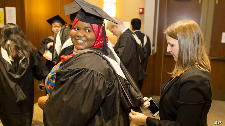 Mariama Bassama is helped with her hood by Charlotte Pandraud before the 2016 graduation ceremony for Hult International Business School, in Boston