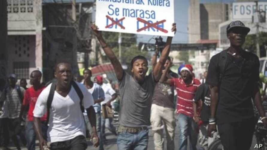 A demonstrator shouts as he carries a sign reading in Creole 'Minusta and Cholera are twins' during a protest in Port-au-Prince, Haiti, 18 Nov 2010