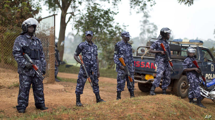 A line of riot police prevent the media and others from approaching Uganda's main opposition leader Kizza Besigye, who was placed under house arrest at his home in Kasangati, Uganda, Feb. 22, 2016.