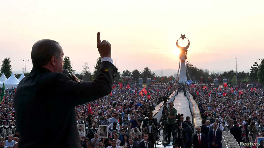 Turkish President Tayyip Erdogan addresses his supporters during a ceremony marking the first anniversary of the attempted coup at the Presidential Palace in Ankara, July 16, 2017.