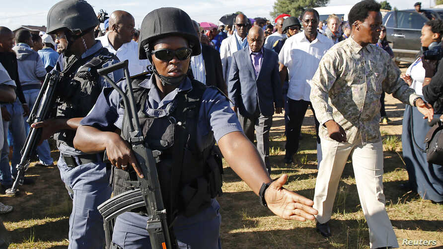 FILE - Members of a security team escort Lesotho politician Thomas Thabane (C) after he cast his vote during the country's national elections in Magkhoakhoeng village, outside the capital Maseru, Feb. 28, 2015. Thabane's estranged wife, Lipolelo Thab