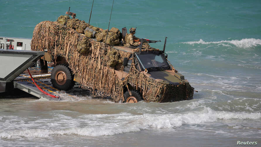 FILE - An Australian troop transporter wades onto Langham beach during military exercises in Queensland, northeast Australia, July 13, 2017.