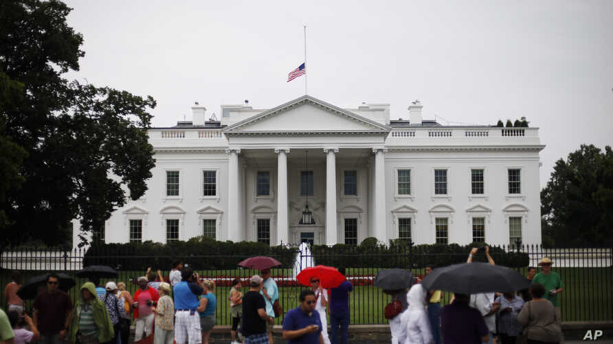 The American flag is seen at half-staff over the White House in Washington, July 20, 2012.