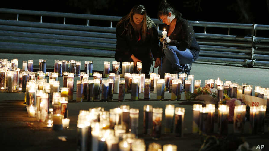 Meriah Calvert, left, and an unidentified woman pray by candles spelling out the initials for Umpqua Community College after a candlelight vigil, Roseburg, Ore., Oct. 1, 2015.